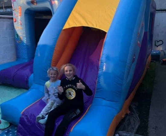 Happy customers of bouncy castle hire cork company Just 4 Leisure - photo of two girls sitting on bouncy castle with thumbs up